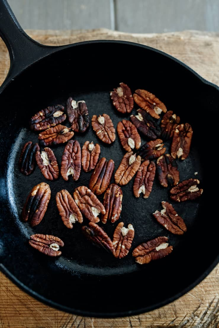 toasted pecans in a cast iron skillet