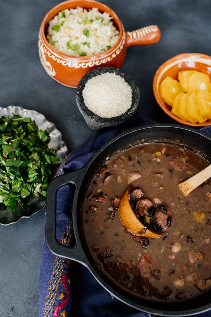 cast iron dutch oven with brazilian feijoada on a patterned blue towel with bowls of garlic butter rice, orange silces, salt and collard greens