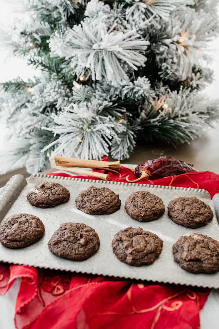 Mexican hot chocolate christmas cookies on a silver tray atop a red linen with cinnamon sticks, a dried chili and a christmas tree in the background