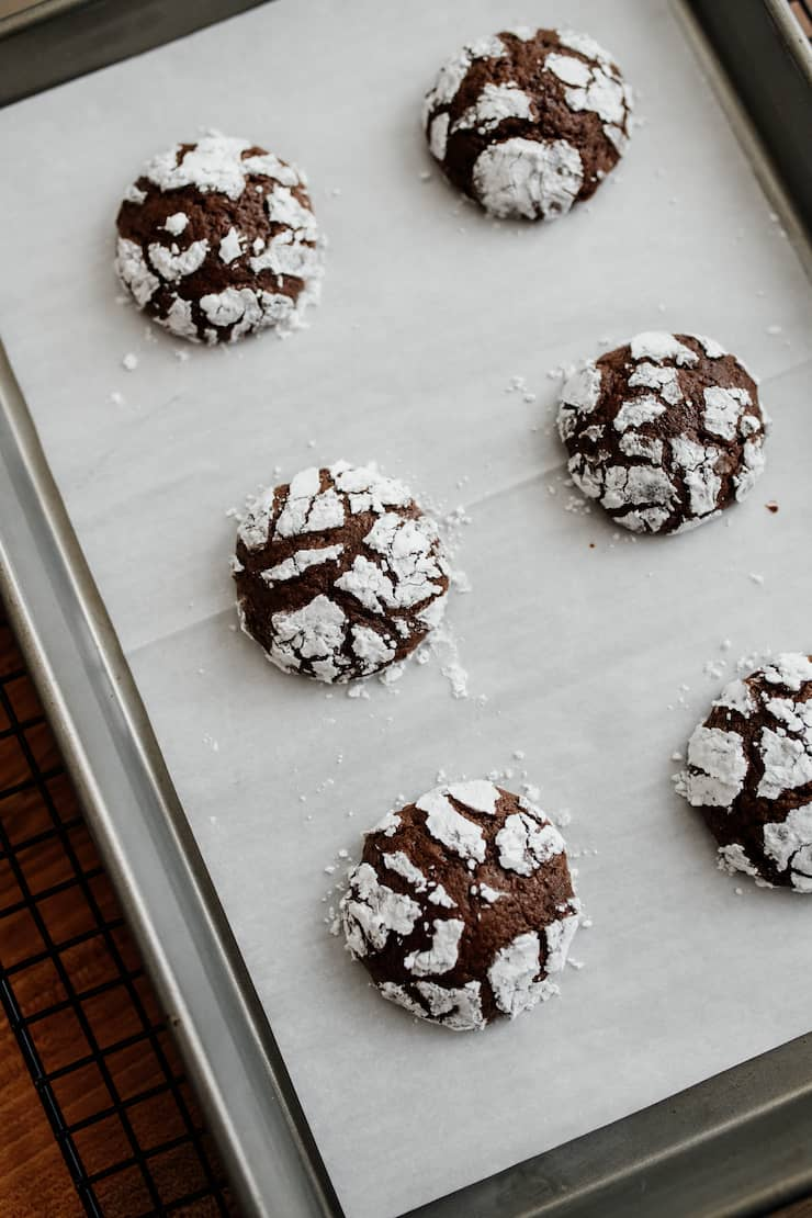 mexican chocolate crinkle cookies after baking on a parchment lined baking sheet