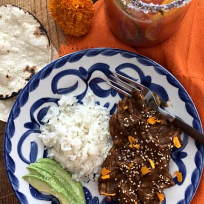 chicken mole on a blue and white plate with white rice and salted avocado