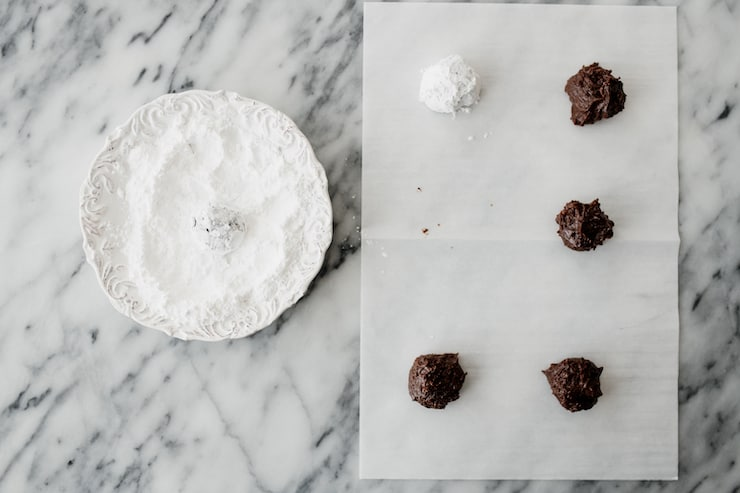 sheet of parchment with rolled cookie dough balls, one of which has been coated in powdered sugar