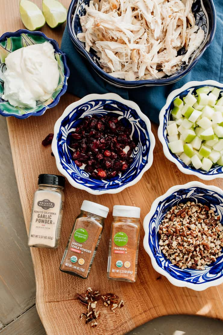 spice jars and bowls of chopped pecans, chopped apples, cranerries, shredded chicken and greek yogurt as mis en place for chicken salad recipe