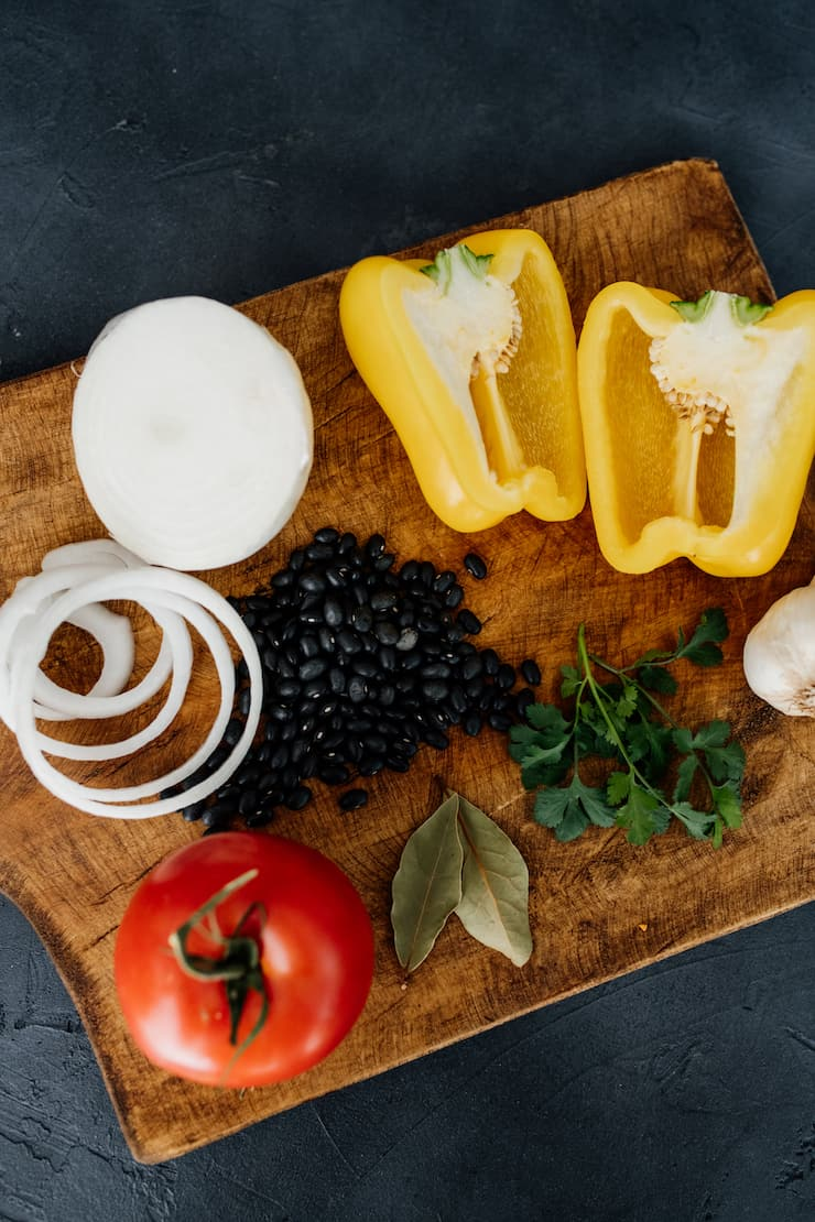 close up of white onion, yellow bell pepper, garlic bulb, parsley, bay leaves, black beans and a tomato on a wood cutting board