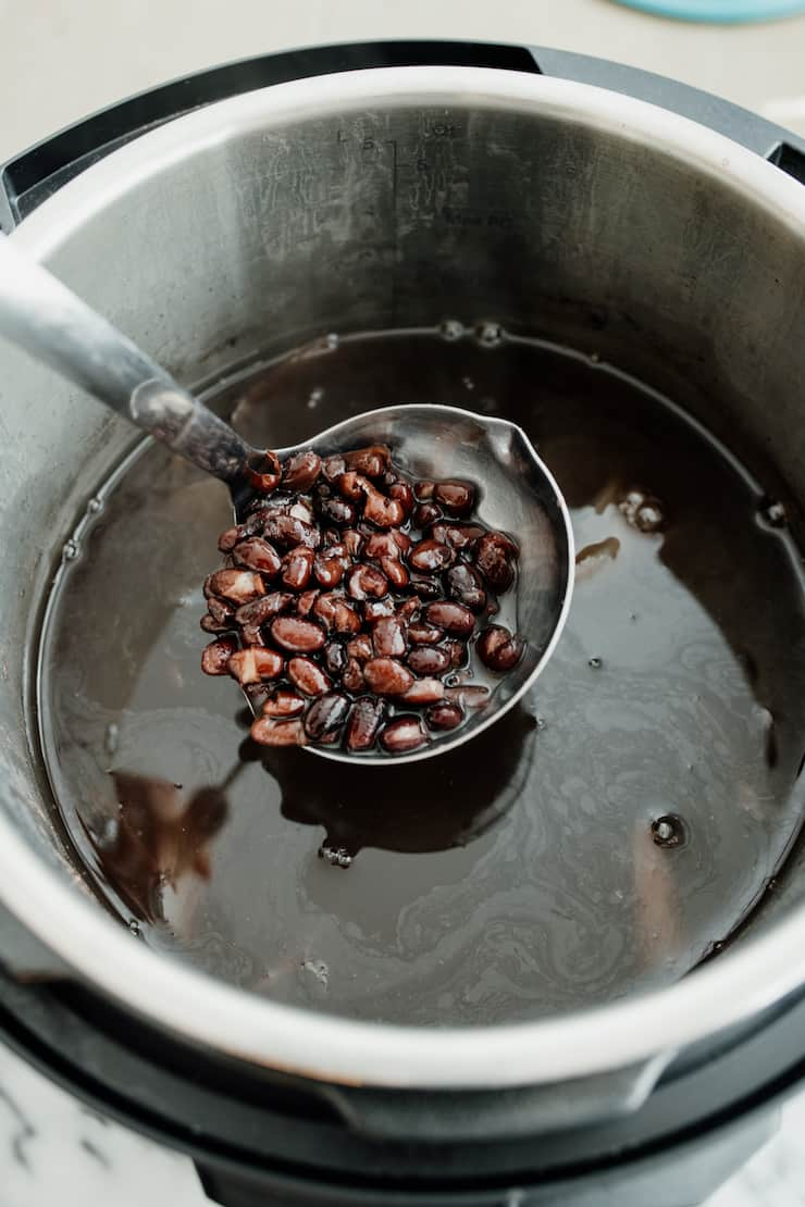 black beans in instant pot with silver ladle