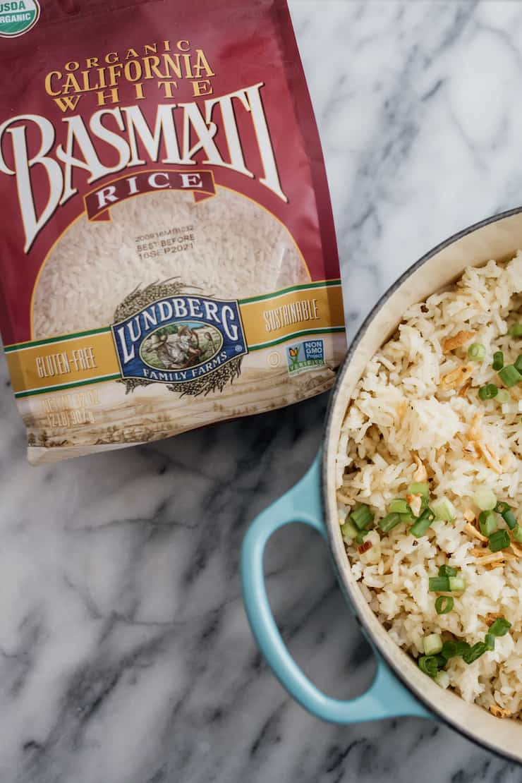 bag of lundberg brand white basmati rice next to turquoise enameled dutch oven with garlic butter rice