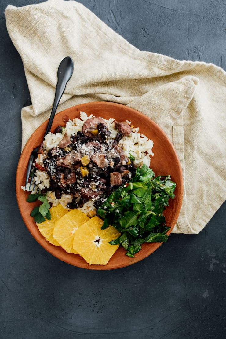 brazilian feijoada (black bean stew) served over garlic rice with sautéed collards and orange slices in an orange bowl