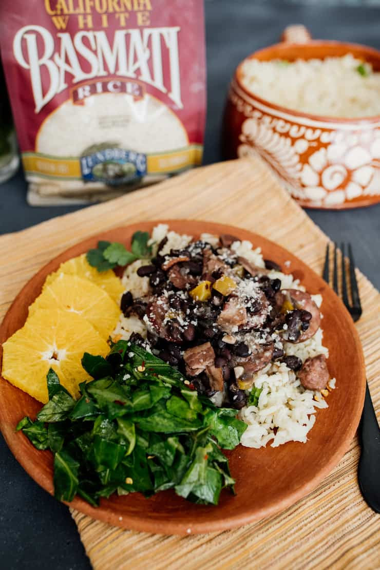 45 degree shot of feijoada over garlic rice with sautéed collards and orange slices with bags of lundberg rice in the background