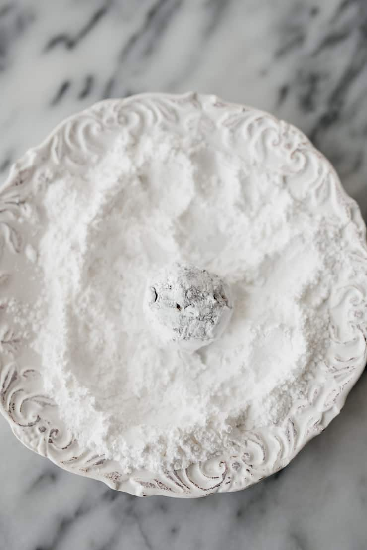 white plate with powdered sugar and a crinkle cookie dough ball that has been coated in powdered sugar