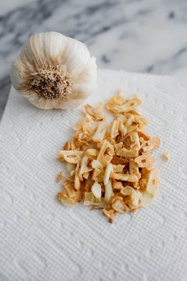 head of garlic with crispy garlic slices on a paper towel