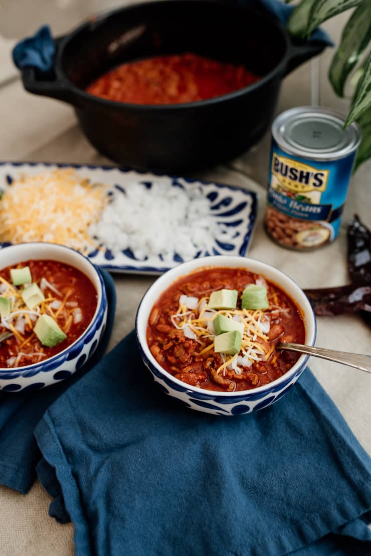 final hero shot of chorizo chili con carne in a blue and white bowl with toppings and a can of bush's pinto beans in the background