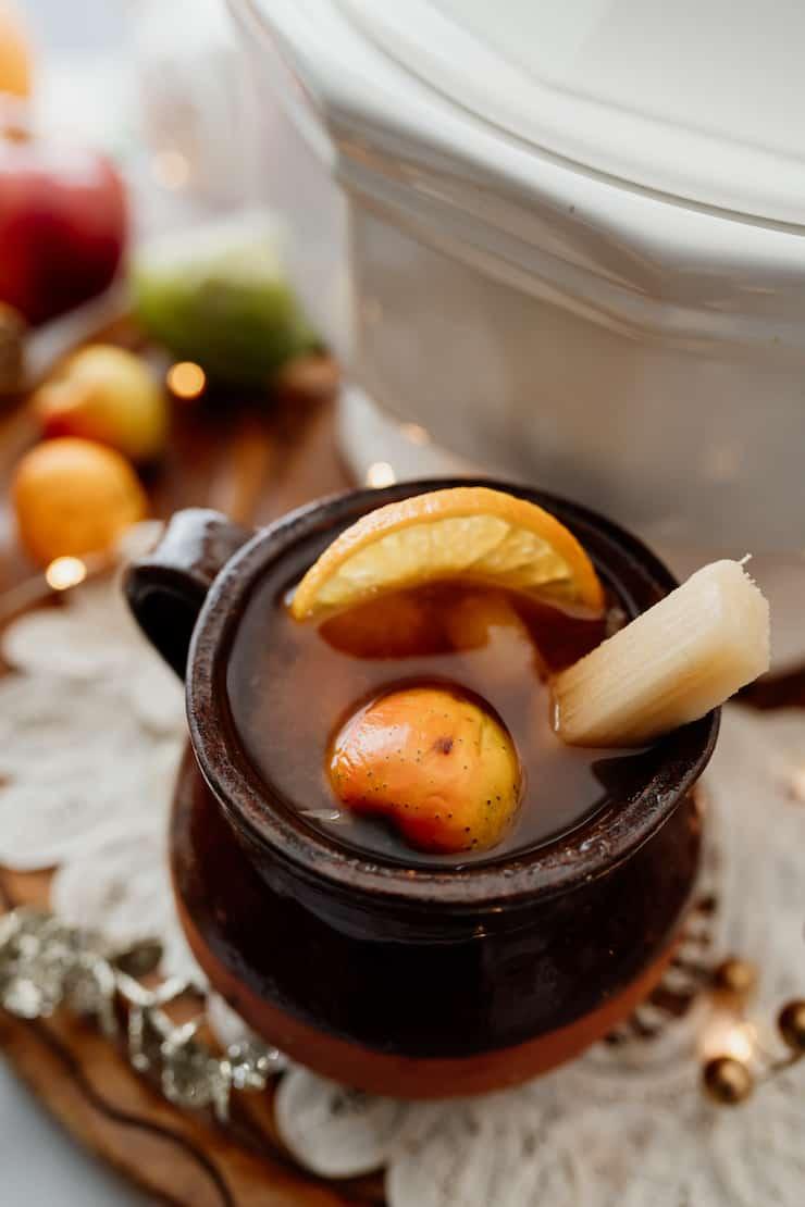 close up shot of ponche navideño in a short mug garnished with tejocote, fresh sugarcane and an orange slice on a white doily