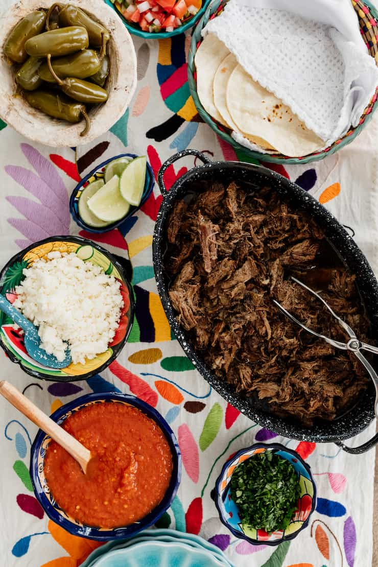 how to set up a serve yourself taco bar with tortillas, suadero style meat, onions, salsa, cilantro and lime wedges on a colorful runner