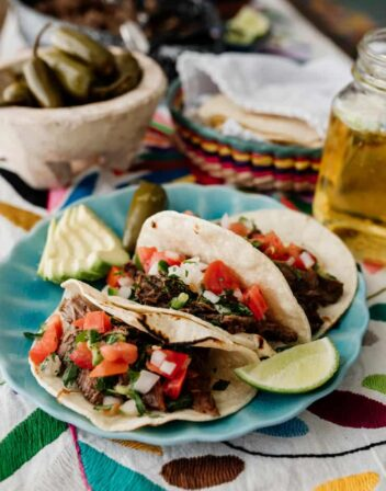 three slow cooker brisket tacos on a turquoise plate topped with pico de gallo and carne deshebrada
