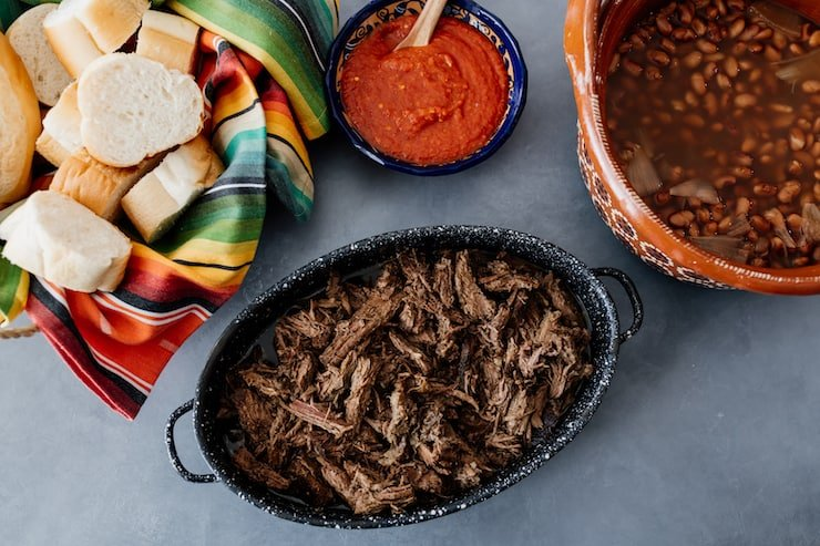 shredded crockpot brisket in a handled black serving bowl with a blue bowl of red salsa, a brown bowl of frijoles de la olla and a striped tea towel lined bread basket with bolillos