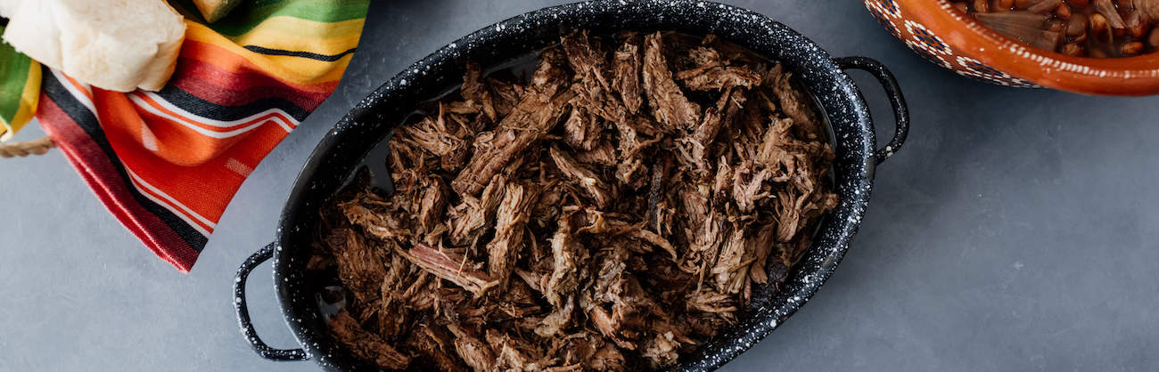 crockpot brisket that has been shredded and placed in a black serving vessel
