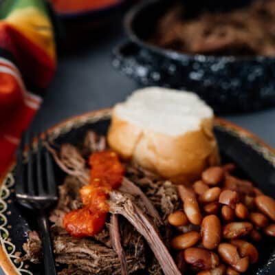 shredded crockpot brisket on a black plate with beans, bolillo and salsa