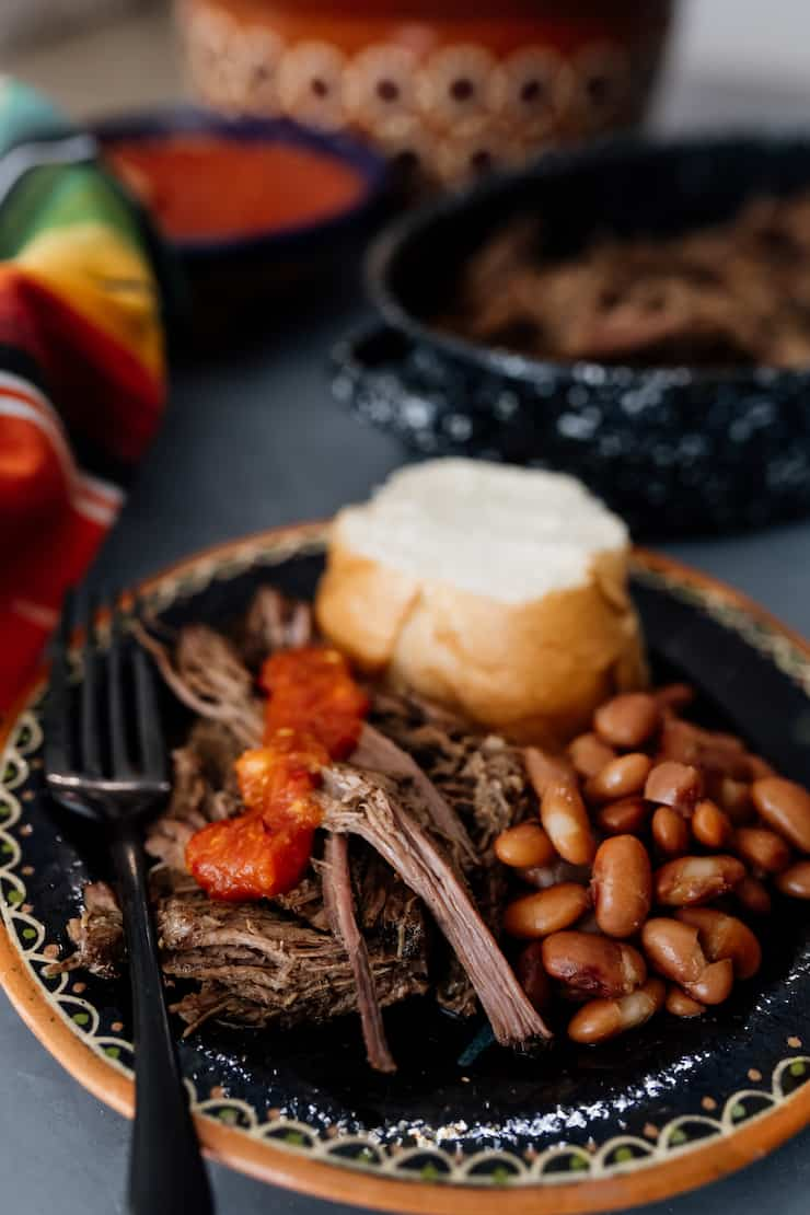 shredded slow cooker beef brisket on a black plate with salsa, beans and a bolillo roll