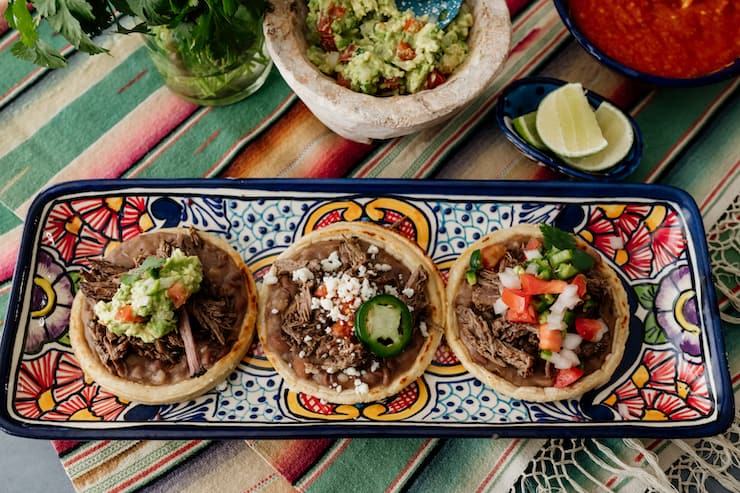 overhead shot of a horizontal rectangular serving platter with three brisket filled sopes