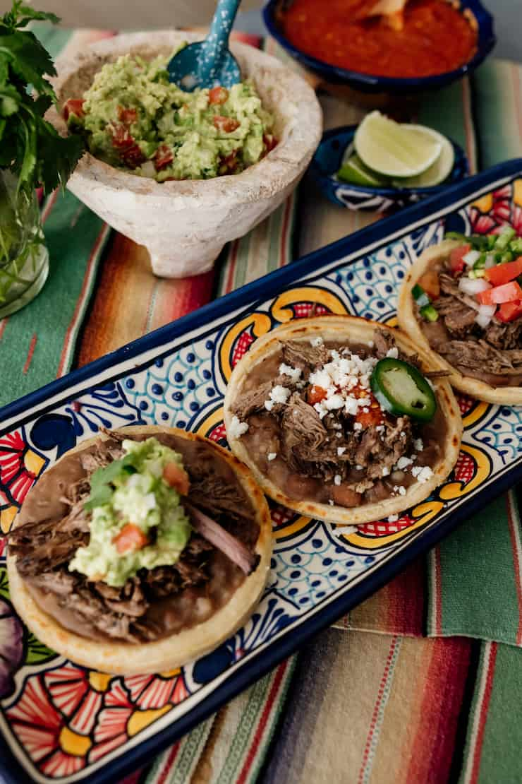 three beef brisket topped mexican sopes on a colorful rectangular serving platter with a bowl of guacamole and salsa in the background