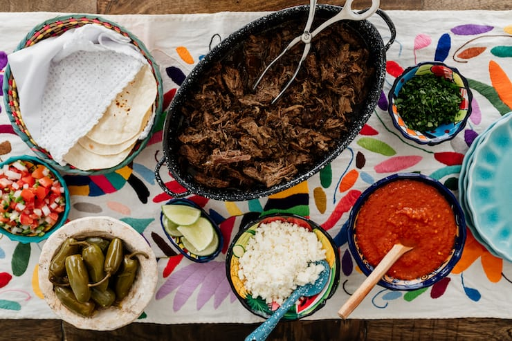 colorful tapestry under a party style taco bar with tortillas, carne deshebrada (suadero), escabeche, salsa, onions and lime wedges