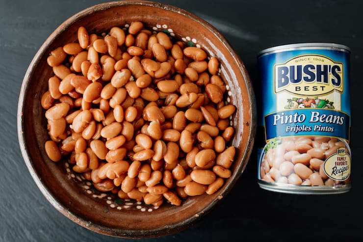 a can of bush's pinto beans next to pinto beans in an earthenware bowl