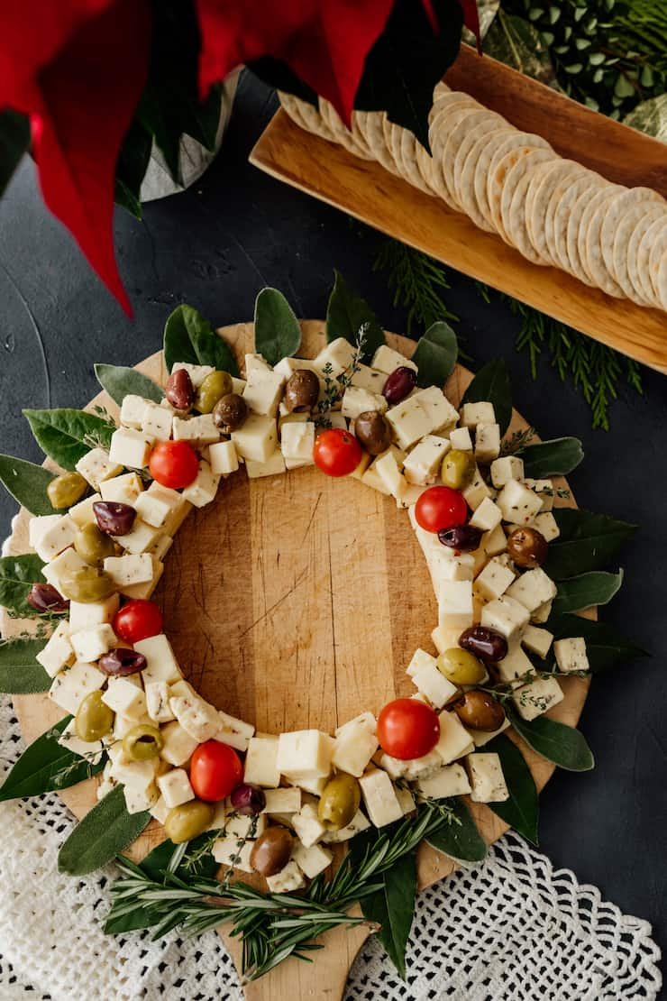 christmas wreath cheese board on a round wooden tray with a side of water crackers