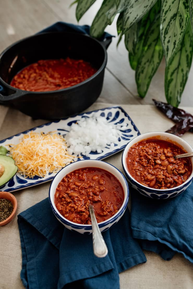 two blue and white bowls filled with chili con carne with a matching rectangular plate with onions, cheese and avocado as toppings