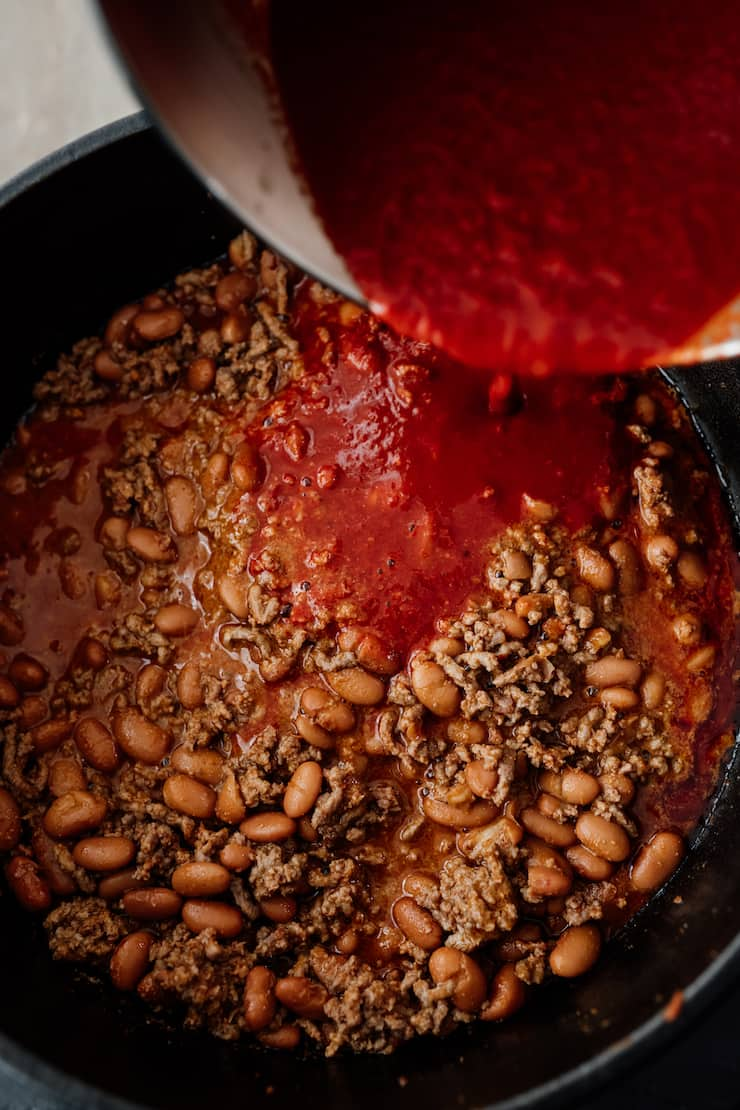 enchilada sauce being added to chorizo chili in a dutch oven