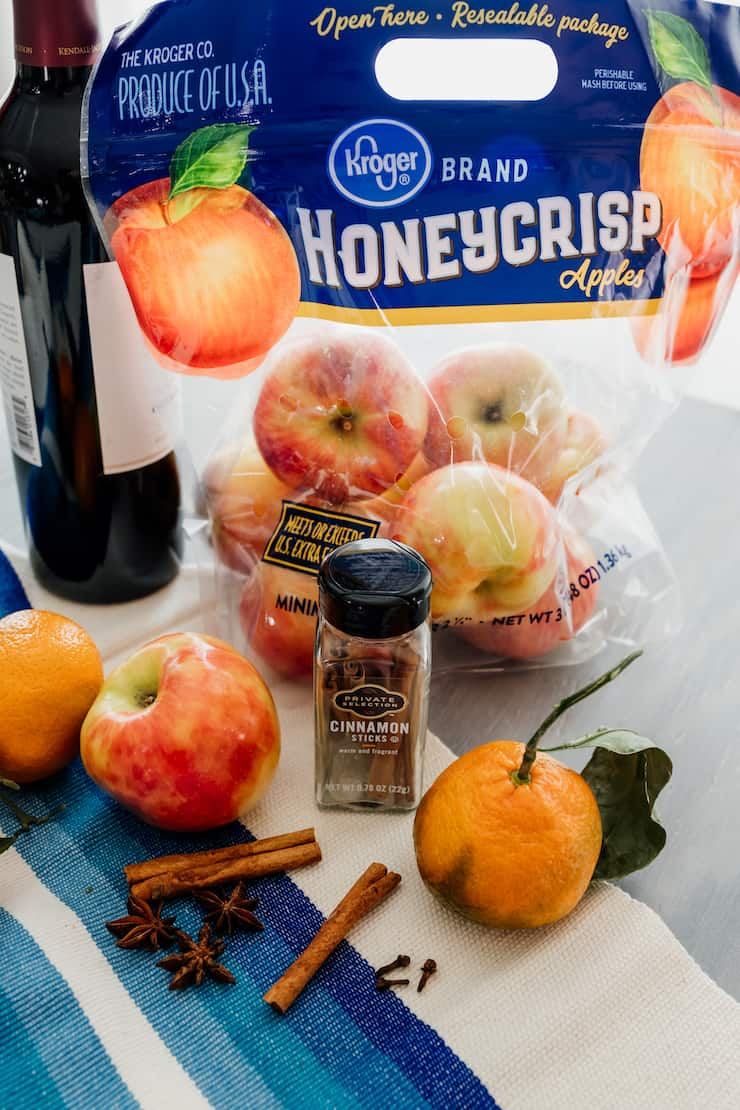 mise en place for mulled wine recipe - bottle of red wine, honeycrisp apples, cinnamon sticks, whole star anise and oranges on the vine