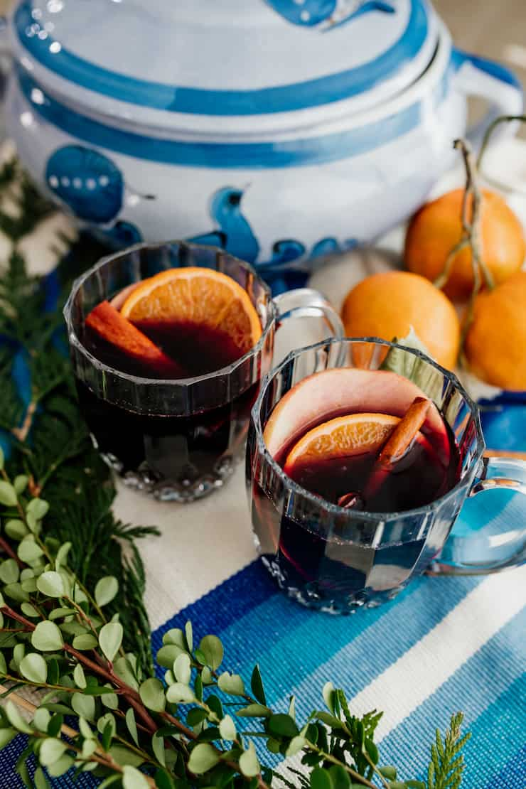 two glass mugs of spiced mulled wine with cinnamon stick and orange slice garnishes on a blue and white tablescape
