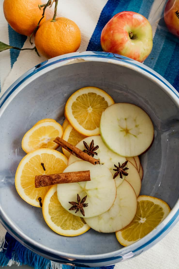 thin slices of apples and oranges in a ceramic bowl with star anise and cinnamon sticks