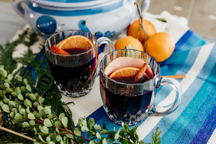 two mugs of spiced mulled wine with cinnamon stick and fruit slice garnishes on a blue and white tablescape with greenery