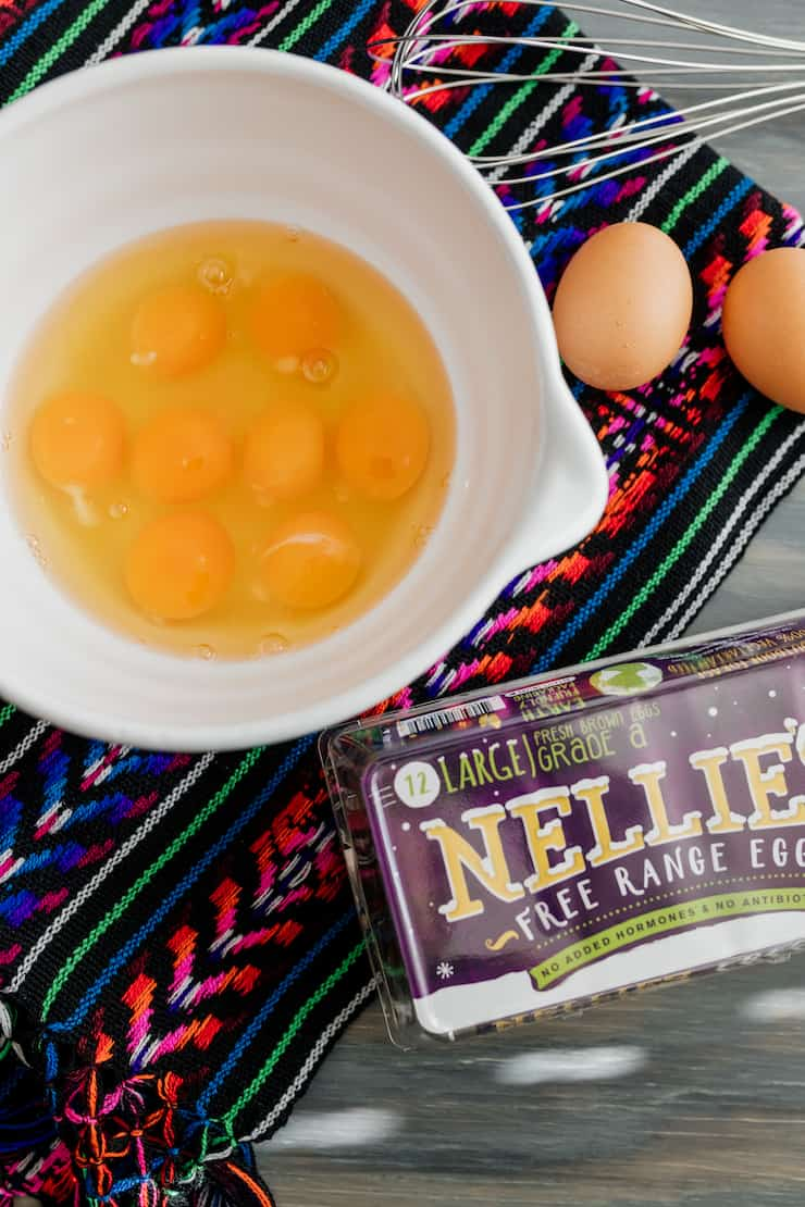 white bowl with farm fresh eggs and a carton of Nellies eggs, and whisk on the side on a colorful Mexican textile