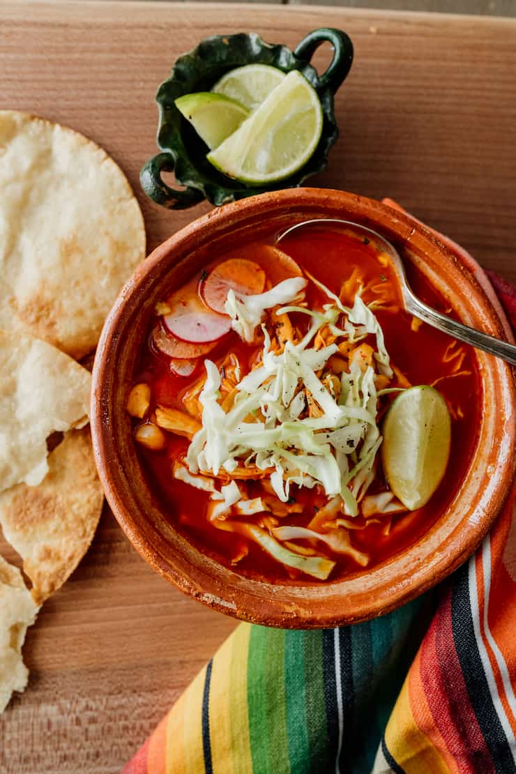 red chicken pozole in a terra cotta bowl with a silver spoon and tortillas to the side