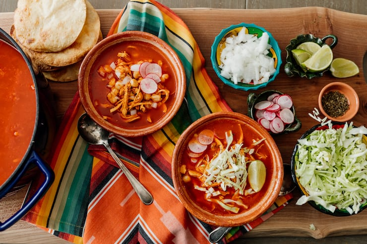 red chicken pozole in terra cotta bowls with small bowls filled with garnishes like sliced radish, chopped onions, sliced cabbage and lime quarters on a colorful fabric lined table
