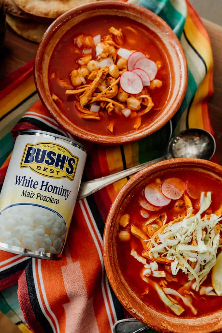 final overhead hero shot of red chicken pozole in terra cotta bowls with silver spoons and a can of bush's white hominy