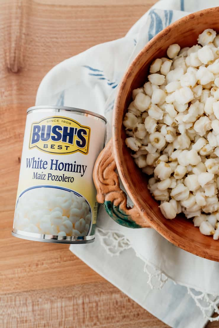 can of bush's white hominy next to an earthenware bowl filled with hominy