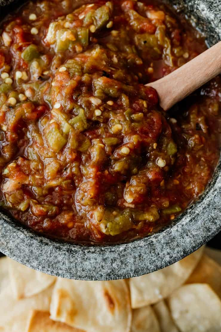 close up shot of homemade salsa with canned tomatoes and green chiles in a stoneware bowl molcajete with a wooden spoon