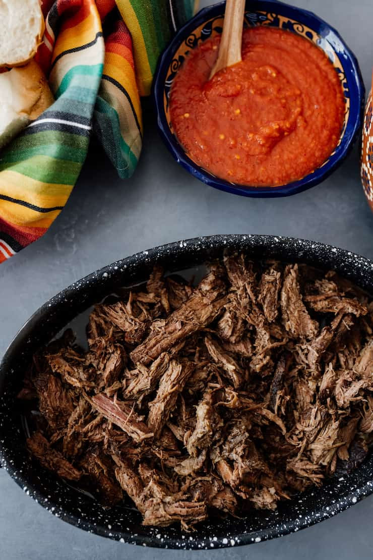 shredded slow cooker beef brisket in a serving dish with a bowl of red salsa and a colorful striped towel on a grey surface
