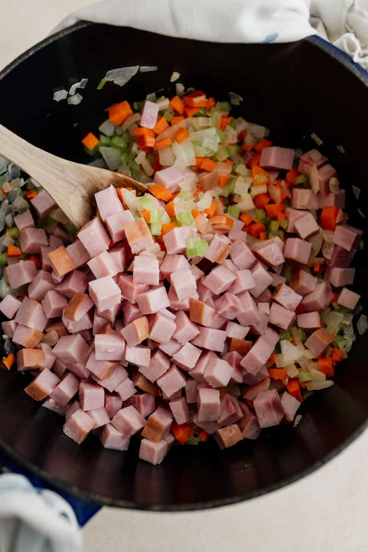 cubed ham added to mirepoix in pot with a wooden spoon
