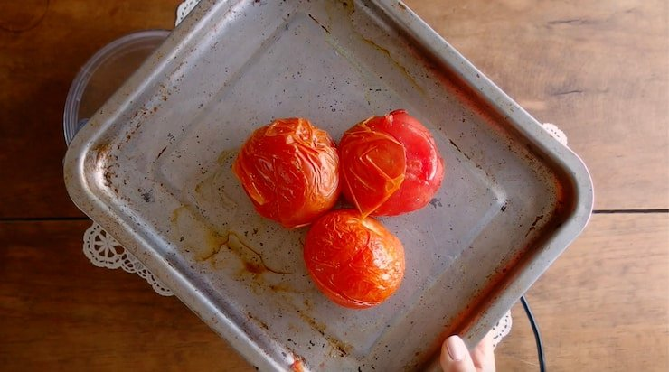 three tomatoes on a sheet pan