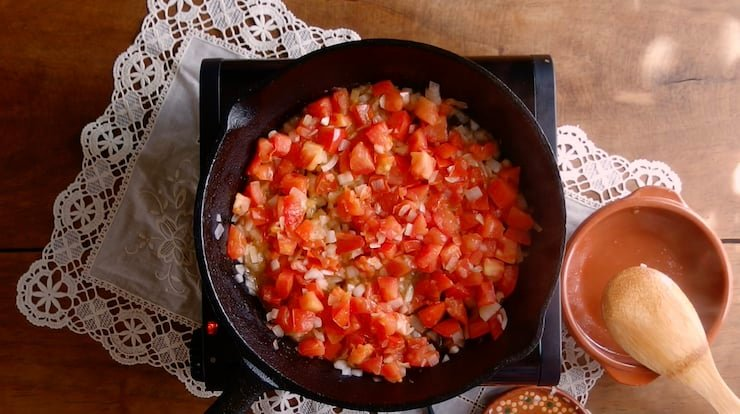 tomatoes and onions sautéing in a skillet for meatball soup