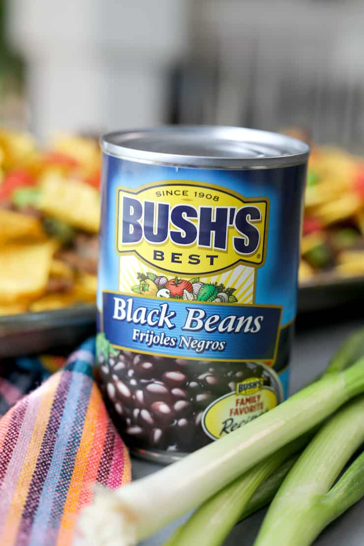 can of bush's best black beans in the foreground and sheet pan nachos in the background
