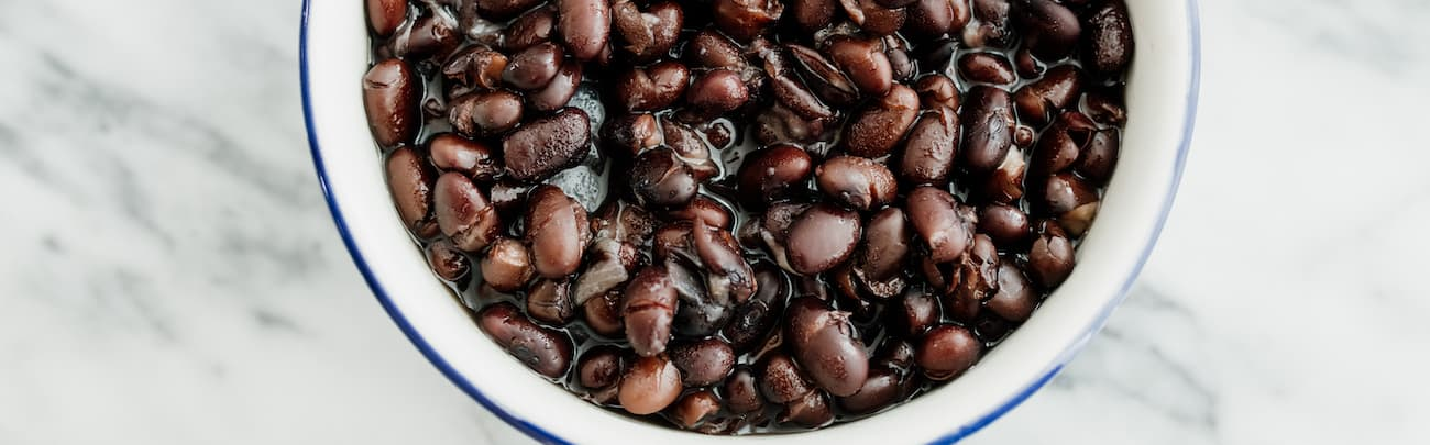 Mexican style black beans in a white bowl with a blue rim