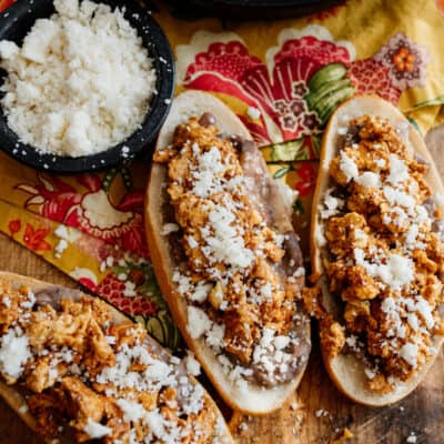 three molletes de huevo con chorizo on a wooden cutting board