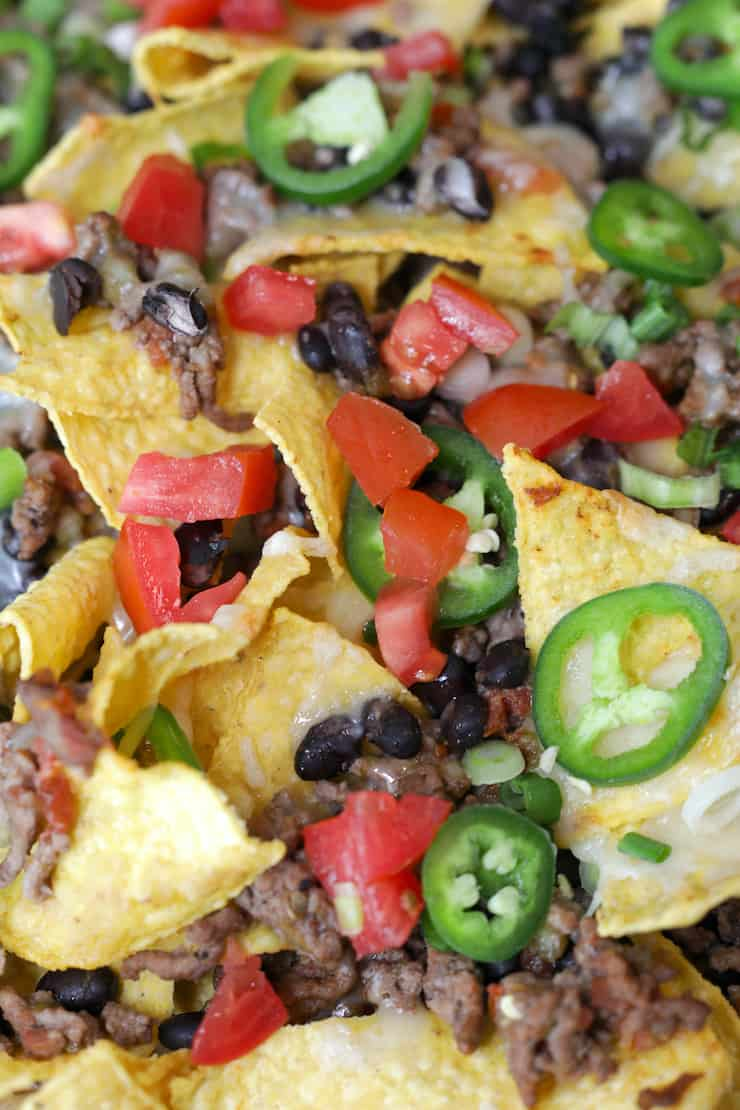 close up shot of classic nachos garnished with sliced fresh jalapeños and pico de gallo