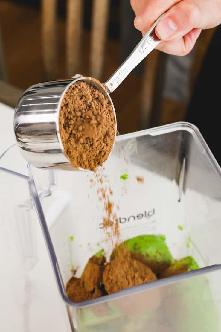 silver measuring spoon pouring cocoa into blender with avocado for vegan chocolate avocado pudding