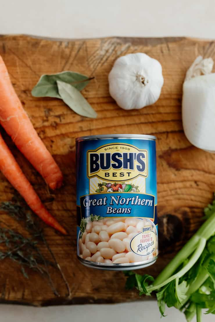 close up of a can of bush's great northern beans on a wooden cutting board with vegetables around it