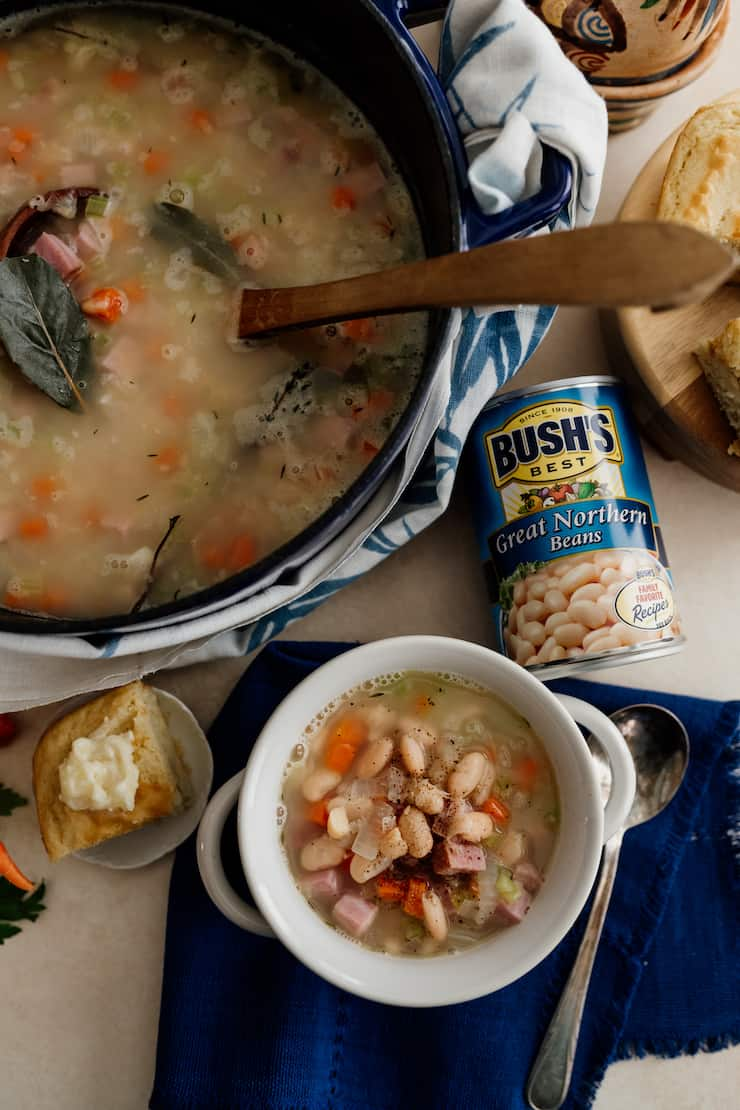 overhead shot of navy bean soup in a pot and in a white bowl with a can of bush's great northern beans and a slice of cornbread
